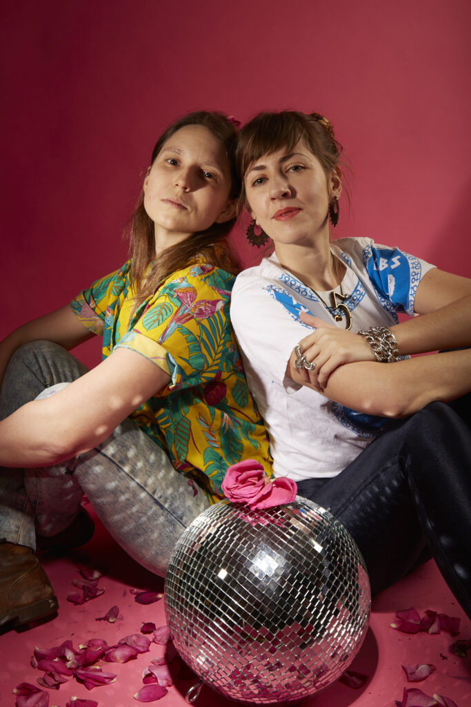Rose and Gala seated back to back in a pink studio. A disco ball is on the ground between them with a pink rose on top and petals scattered all around. roses is wearing a floral yellow shirt and cargo. Gala is wearing a white t-shirt with blue blocks that says lezbos on it and dark pants. They are gazing serenely at the camera